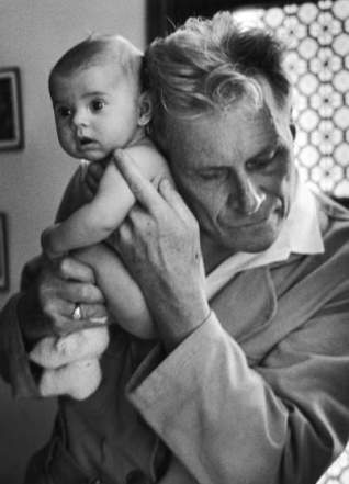 Blind doctor Albert A. Nast holding his ear to the back of a 3 month old instead of using a stethoscope.